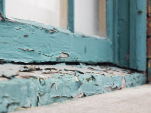 Closeup of an old window sill with paint peeling and flaking off